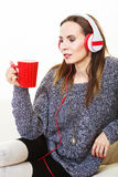 Woman with headphones listening music. People leisure relax concept. Woman casual style red big headphones listening music mp3, sitting on couch at home relaxing Royalty Free Stock Photos