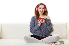 Woman with headphones listening music. People leisure relax concept. Woman casual style red big headphones listening music mp3, sitting on couch at home relaxing Royalty Free Stock Photography