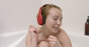 Relax with music in bath. Woman with headphones listening music and singing in bath stock video