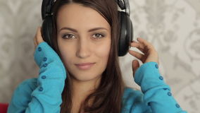 Woman in Headphones Listening Music on the Sofa stock footage