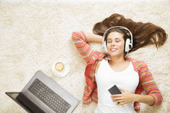 Woman in Headphones Listening to Music, Girl with Mobile Phone. Woman in Headphones Listening to Music, Girl Dreaming with Mobile Smart Phone, Laptop Computer royalty free stock photo