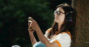 Woman in Headphones Listening to Music in Park stock video