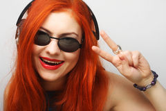 Woman with headphones listening to music. Rock style woman with headphones listening to music royalty free stock photography
