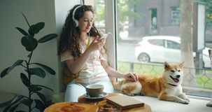 Woman in headphones listening to music using smartphone stroking pet in cafe. Young woman in headphones is listening to music using smartphone and stroking pet stock video