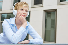 Woman with headphones looking pensively Royalty Free Stock Images