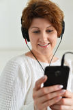 Woman in headphones looks at smartphone Royalty Free Stock Photos