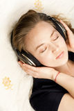 Woman with headphones lying down on sofa in lounge Royalty Free Stock Photo