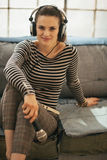 Woman with headphones and microphone in loft Royalty Free Stock Photography