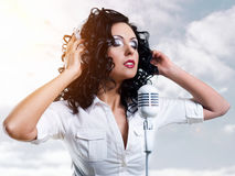 Woman with headphones and microphone over clouds Stock Photos