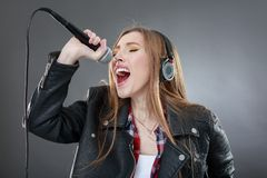 Woman with headphones and microphone singing Royalty Free Stock Photography