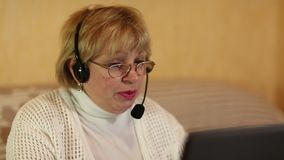 Woman with headphones with microphone talks to a customer via computer stock footage