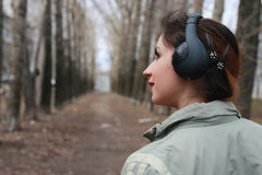 Woman with headphones in park autumn Stock Images