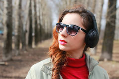 Woman with headphones in park autumn stock photography