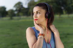 Woman with Headphones in the Park Royalty Free Stock Photos