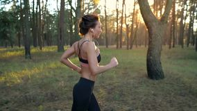 Close up of woman with headphones running through an autumn forest at sunset. Filmed at different speeds - normal and stock video footage