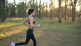 Close up of woman with headphones running through an autumn forest at sunset. Filmed at different speeds - normal and stock footage