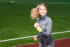 Woman with headphones running in the stadium Stock Photos