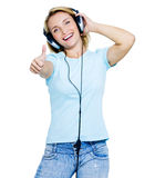 Woman with headphones showing  thumbs-up Royalty Free Stock Photography