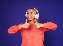 Woman in headphones showing thumbs up. Studio shot Royalty Free Stock Image