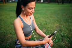 Woman in headphones sitting on grass and relax Royalty Free Stock Photo
