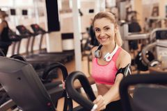 Woman with headphones running on treadmill at the gym. They look happy, fashionable and fit. royalty free stock photos