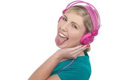 Woman with headphones on sticking her pierced tongue out Royalty Free Stock Photography