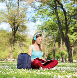 Woman with headphones studying in park Stock Photography