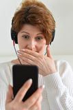 Woman in headphones with surprise looks at smartphone Royalty Free Stock Photography