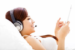 Woman with headphones and tablet on the bed Stock Images