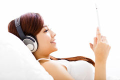 Woman with headphones and tablet on the bed Royalty Free Stock Image