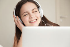 Woman in headphones takes pleasure from music Royalty Free Stock Photography