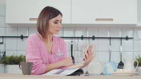 Woman with headphones talking or listening music using smartphone. Attractive woman with headphones talking or listening music using smartphone in the kitchen stock footage