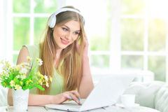 Woman in headphones   using  laptop Royalty Free Stock Images