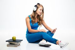 Woman with headphones and using smartphone on the floor Stock Photo