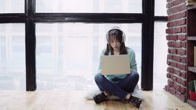 Woman in headphones working on a laptop stock video