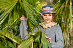 Woman with headscarf next to palms Stock Photography