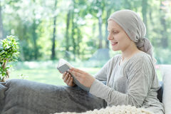 Woman in headscarf reading book. Relaxing in cancer treatment hospital Royalty Free Stock Images