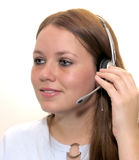 Woman with a Headset. Young pretty woman wearing a phone headset with white background. Good detail and nice complexion royalty free stock image