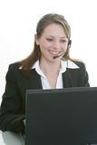 Woman with headset and computer. Woman with headset typing on a laptop stock photos
