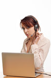 Woman in the headset and with a computer Royalty Free Stock Image