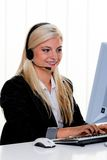 Woman with a headset and computer Hotline. Young woman with a headset and computer hotline Stock Image