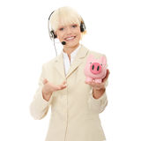 Woman with headset holding piggy bank Royalty Free Stock Images
