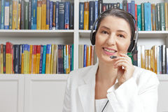 Woman headset microphone office books. Friendly smiling mature woman with headphones and white blazer in a library, talking with someone via a video call, as Royalty Free Stock Images