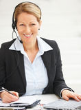 Woman with headset in office Stock Images