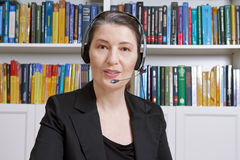 Woman headset office telemarketing telesales. Friendly middle aged woman with headphones and black blazer in an office with lots of books, talking with someone Royalty Free Stock Photos