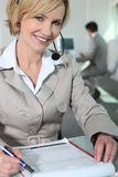 Woman with headset and questionnaire. Woman smiling with headset and questionnaire Royalty Free Stock Photo