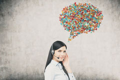 Woman with headset and speech bubble. Side view of girl with headset standing near concrete wall with colorful speech bubble above her head. Concept of hotline Stock Photo
