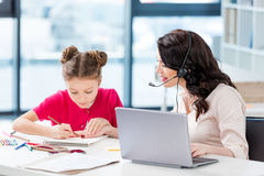 Woman in headset using laptop and looking at daughter drawing at workplace Royalty Free Stock Photography