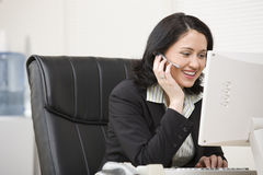 Woman in headset working at computer. Woman on hands free headset working at computer Stock Image