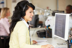 Woman With Headset Working At Desk In Busy Creative Office Stock Photography